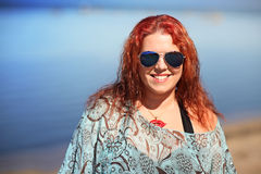 Rödhårigt plus formatkvinnan som vilar på kust arkivfoton