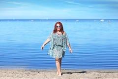 Rödhårigt plus formatkvinnan som vilar på kust royaltyfri bild