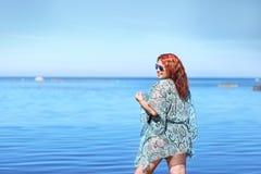 Rödhårigt plus formatkvinnan som vilar på kust royaltyfri fotografi