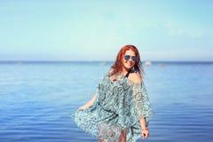 Rödhårigt plus formatkvinnan som vilar på kust royaltyfria bilder