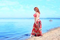 Rödhårigt plus formatkvinnan som vilar på kust arkivbilder