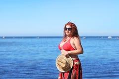 Rödhårigt plus formatkvinnan som vilar på kust royaltyfri foto