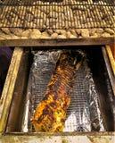 Röding som grillar den hela grisköttfransyskan över varma kol royaltyfria foton