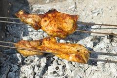 Rödlätt kebab på steknålar Styckena av kött som grillas på kol Nära övre, selektivt fokuserar royaltyfri bild