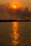 Rök över den Okavango floden Arkivfoto