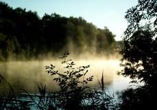Rök över vattnet på soluppgång arkivfoto