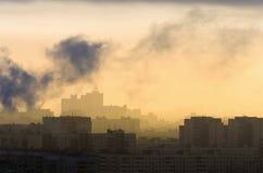 Rök från industriella lampglas på gryningstaden Arkivbild