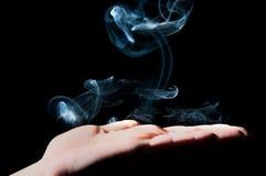 Rök och hand arkivfoto