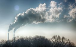 Röka från industriella lampglas mot blåttskyen förorening Royaltyfria Foton