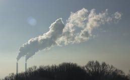 Röka från industriella lampglas mot blåttskyen förorening Arkivfoto