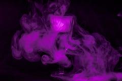 Röka in i coctailexponeringsglas på en svart bakgrund Häxadryckbakgrund för allhelgonaafton Ovanlig stångdrink royaltyfria foton