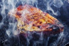 Röka och ånga löneförhöjningen från en grisköttbiff på gallerpannan Arkivfoto