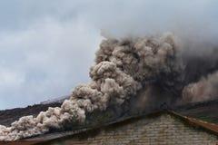 Röka och askaen från den vulkanSinabung spridningen längs jordningen Royaltyfri Foto