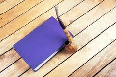 Röka röret och boken Royaltyfri Foto