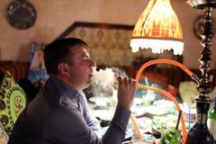 Röka shisha för man Arkivbilder