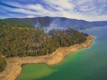 Röka stigning upp från skog på kuster av den Tumut floden royaltyfri fotografi