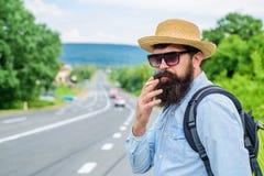Röka vana Röka cigaretten för lång resa Man med skägget och mustasch i sugrörhatt som röker cigaretten, väg arkivbild