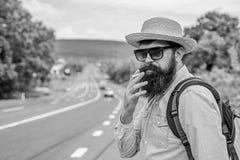 Röka vana Röka cigaretten för lång resa Man med skägget och mustasch i sugrörhatt som röker cigaretten, väg arkivfoton