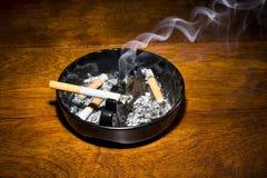 Rökande cigarett i askfat Royaltyfri Foto