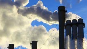 Rökbuntar av kraftverk och blå himmel i bakgrund stock video
