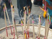 Rökelse klibbar bränning och i ett altare royaltyfria bilder