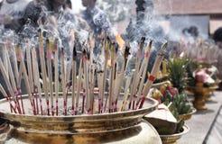 Rökelse klibbar bränning och i ett altare fotografering för bildbyråer
