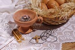 Rökelsekar, stearinljus, kors och ägg i ett rede på en tabell Arkivbild