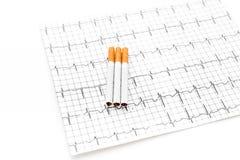 rökning för cigarettfarapacke Cigaretter på kardiogram på vit bakgrund royaltyfri bild
