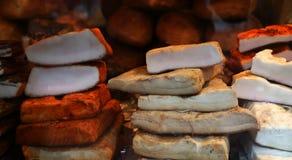 Rökt bacon och bacon med paprika som staplades av olika format, visade till salu på en vintermässa royaltyfria foton