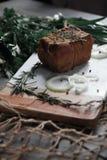 Rökt bacon som ligger på en skärbräda Royaltyfri Bild
