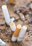 Rökt cigarett i sand. royaltyfri fotografi