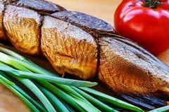 Rökt fisk på skärbräda med tomat- och salladslökcloseupen Arkivbilder