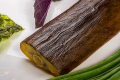 rökt garfish med limefrukt, basilika, salladslökar, chili, norichiper, kryddor, olivolja i en vit keramisk maträtt, på en trätabe arkivfoto