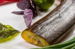 rökt garfish med limefrukt, basilika, salladslökar, chili, norichiper, kryddor, olivolja i en vit keramisk maträtt, på en trätabe arkivfoton