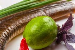 rökt garfish med limefrukt, basilika, salladslökar, chili, norichiper, kryddor, olivolja i en vit keramisk maträtt, på en trätabe royaltyfria bilder