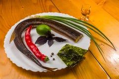 rökt garfish med limefrukt, basilika, salladslökar, chili, norichiper, kryddor, olivolja i en vit keramisk maträtt, på en trätabe arkivbilder