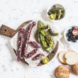 Rökt korv, grillade peppar, oliv och ättiksgurkor på en ljus bakgrund Arkivfoto