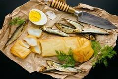 Rökt små stackare och tioarmad bläckfisk, kokt ägg och ny dill på papper Arkivbilder