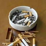 Rökte cigaretter i det vita askfatet och matchsticken Royaltyfri Bild