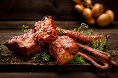 Rökte kött och korvar En uppsättning av traditionella rökte kött och korvar: skinka saltad och rökt skinka, grisköttfransyska, he arkivfoto