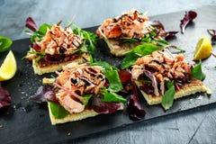 Rökte laxflingor på sallad bäddar ned, och den irländska potatisen bantar mellanmål, aptitretare Arkivfoto