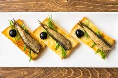 Rökte sardiner på rostat bröd Arkivbilder
