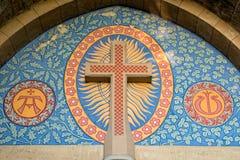 Römisch-katholisch kreuzen Sie vorbei den Eingang einer Kirche Lizenzfreie Stockbilder