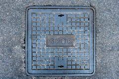 Römischer Kanaldeckel des Eisens auf der Straße Stockfotografie