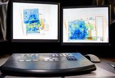 Röntgen Sie Systemscannen eines Kastens mit einer Sprühflasche, einer Flasche Wasser, einem Laptop und einer Kameratasche Stockfotografie