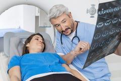 Röntgenstråle för doktor Explaining till patienten som ligger på CT-bildläsningsmaskinen arkivfoto