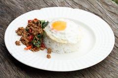 Rör basilika och det stekte ägget med lagade mat ris Arkivbild