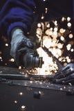 Rör för industriarbetareklippmetall med många gnistastruntsaker i bakgrunden Royaltyfri Bild
