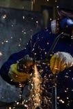 Rör för industriarbetareklippmetall med många gnistastruntsaker i bakgrunden Royaltyfria Bilder