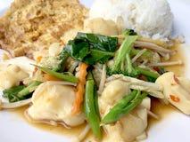 Rör grönsaker med tofuen i kinesisk stil med skysås och thai stilomelett med ris i den vita plattan på bakgrund Vegetari royaltyfri foto